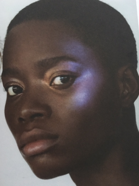 Black woman with very strong illuminator makeup on her cheekbones
