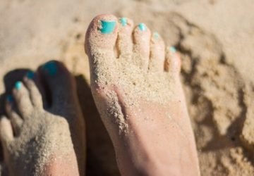 barefoot in the sand with blue nail polish
