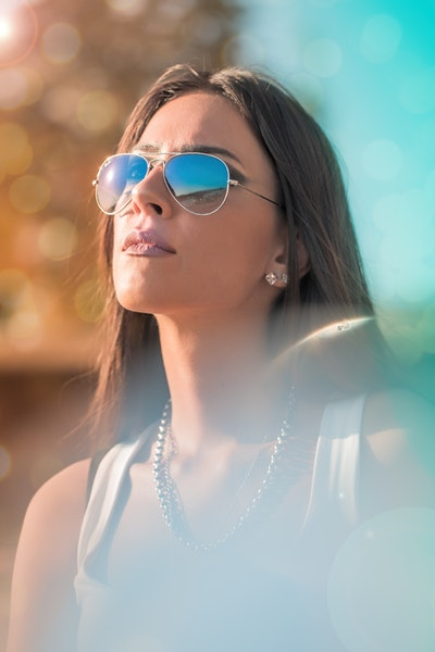 woman with bronzed skin in sunglasses, looking up to the sky