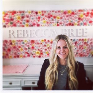 Rebecca bree in her Boutique, in front of the Rebecca Bree sign