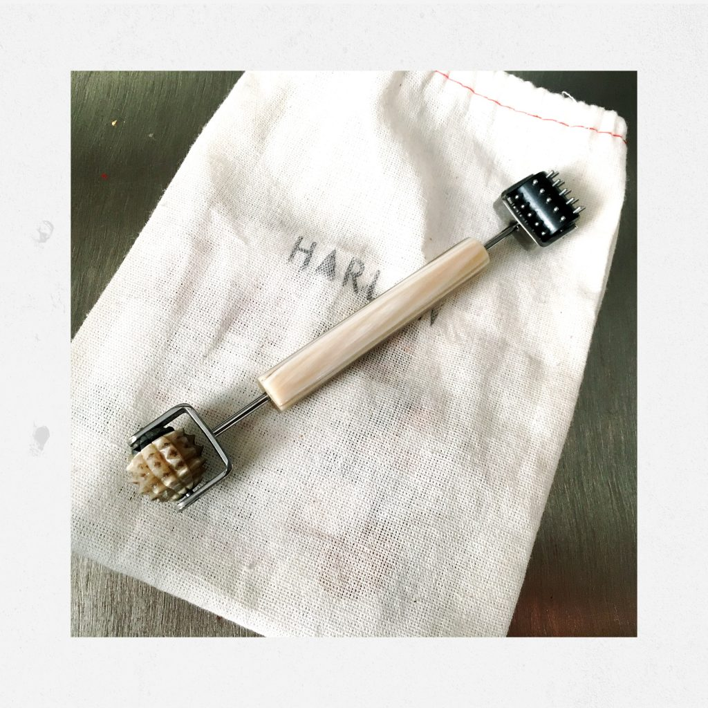 photo of yin yang facial roller from Chan Beaute - a two needed facial roller on a metal table