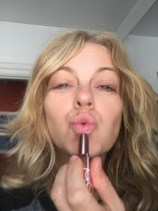 Photo of My Life In Makeup's author Wendy Snowdon trying on Afterglow lip balm by Nars and doing a pouty face selfie