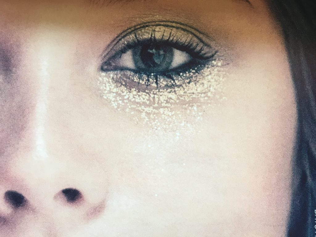 festival eye makeup, gold glitter eye make, close up of woman with brown eyes wearing gold vegan glitter eyemakep, on lid and under her yes